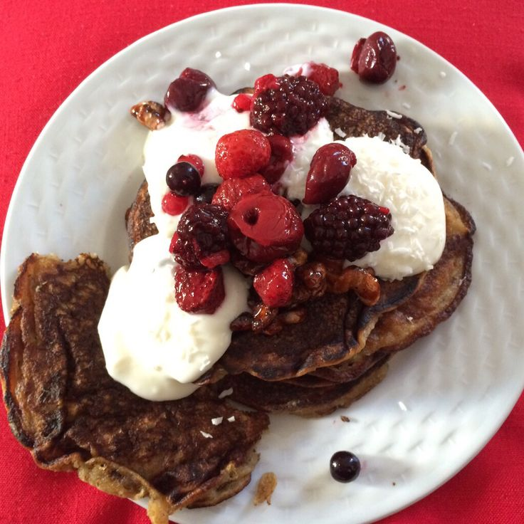 Vegan pancakes with mixed berries, coconut soya yoghurt, and candied walnuts.