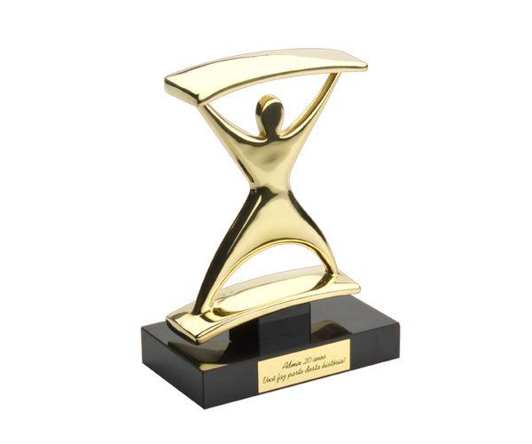 Troféu Exclusivo Ampulheta Peça: bidimensional, 19,5cm de altura. Material: bronze polido (dourado). Base: madeira com fórmica preta 17x10x3cm e 4,5x4,5x2cm. Placa cortesia: 8,5x3cm. Produto exclusivo, desenvolvido exclusivamente para este cliente. Não reproduzimos esta arte, favor consultar produtos similares no portfólio.