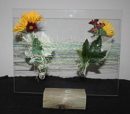 Bloemstuk maken in bloemenbuisjes op een glazen plaat met gerbera's, chrysanten en skeletblad