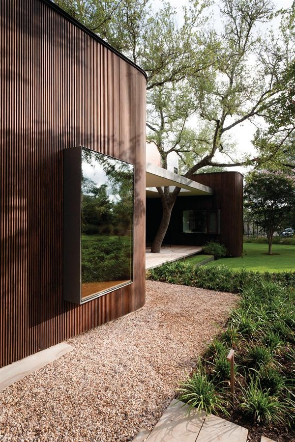 alterstudio, Austin TX  The garage includes a rounded element cladded in slatted wood that serves as interior storage, and that's repeated several times on the home's exterior.
