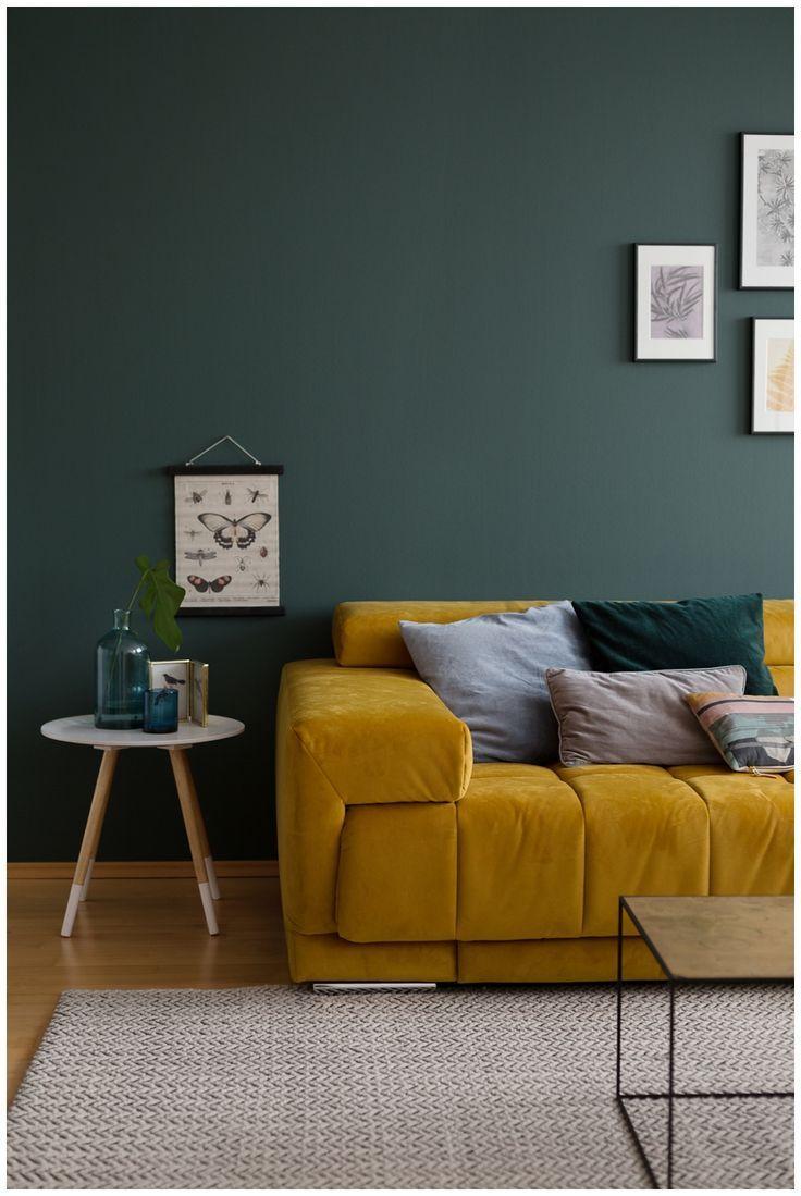 gruene Wandfarbe im Wohnzimmer mit ockerfarbenem Samtsofa