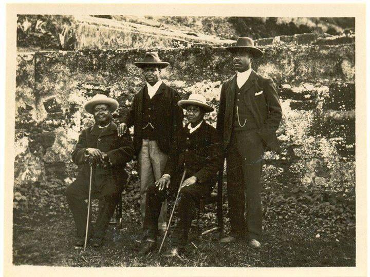 Ngungunhane (sentado à esquerda), Godide (de pé com a mão no ombro do pai), Molungo (sentado) e Zixaxa (de pé), no dia do baptismo do grupo (16 de Abril de 1899).