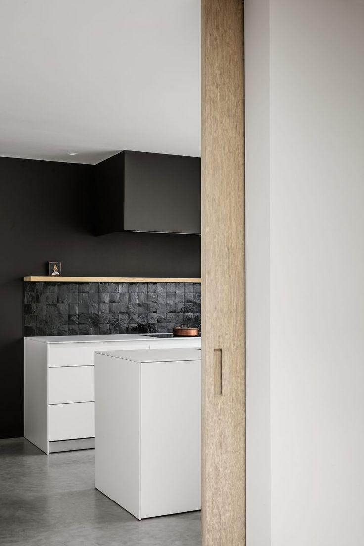 Love the dark ceramic tile backsplash against the stark white Euro style cabinets in this minimalist kitchen