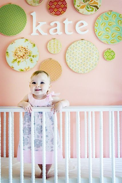 nursery wall - cover different sized embroidery hoops with fabric to hang cute and colorful circles around baby's name spelled out with wooden letters. Love now I need My little girl and vintage barbie outfits this room is complete! -note from Marla- would love to use Aubrey's old shabby chic sheets from her crib over her big girl bed.