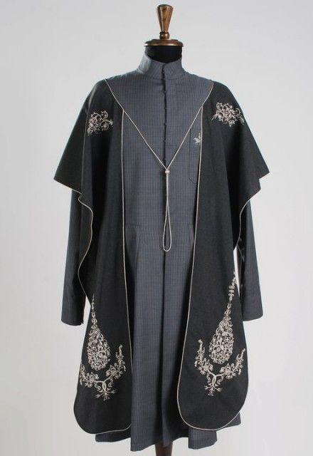 """Традиционная общегрузинская мужская одежда. Серая шерстяная чоха с закрытым воротником-стойкой, нагрудными карманами. Поверх носится """"кабалахи"""" - деталь одежды из тонкой шерсти, расшитое или орнаментированное. Обычно носится на плечах, связывается тесьмой. Легко превращается в головной убор, защищающий всадника от ветра, холода и пыли."""