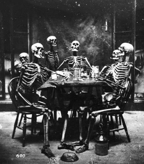 Six skeletons smoking around the dinner table, circa 1865. (Photo by London Stereoscopic Company/Hulton Archive/Getty Images).