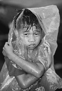 Filipino street child trying to stay dry in the streets of Manila where he lives