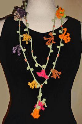 Cordón de flores tejido a crochet en hilos de colores verde claro, amarillos, fucsia, naranjas, lila y marrones, decorado con abalorios