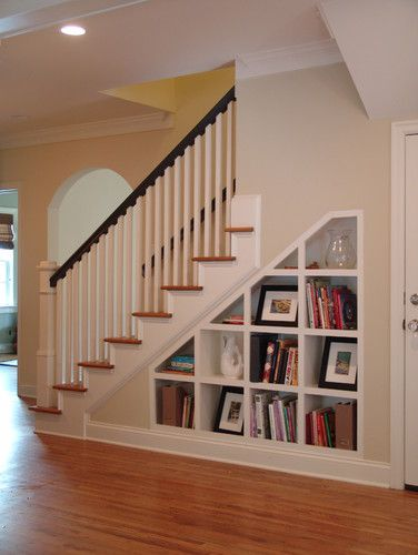 Shelves Under Stairs - shelves same color as the trim with dark handrail & white spindles on stairs.