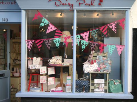 What a colourful shop display! Cute bunting to dress the window too :)