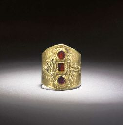 500s Anglo-Saxon: With broad ribbon gold hoop expanding to the bezel, the bezel decorated with vertical column of three garnet inlays in raised mounts, a square inlay in the centre with circular inlay above and below, flanked by scrolling filigree work at either side, punched triangular decoration around the borders with hatching at the edge, hoop split 20mm diam.; weight 7.43 grams