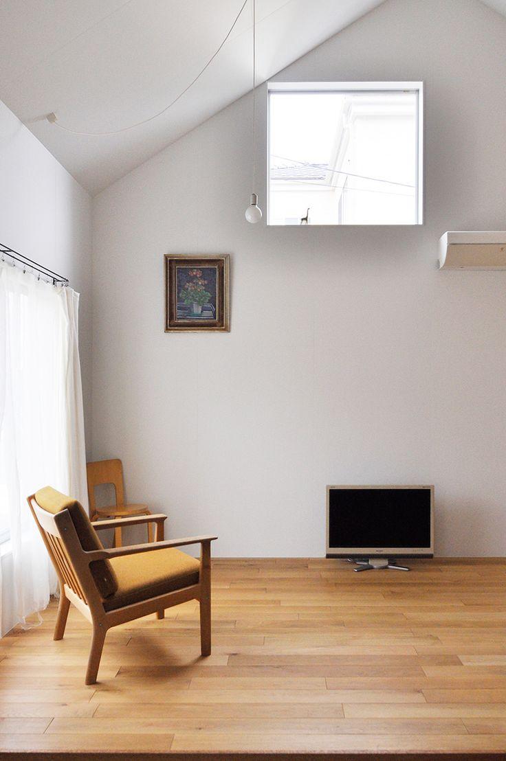 リビングに置かれた椅子はハンス・ウェグナー。高めの場所に開けられた窓が壁の圧迫感を和らげる。