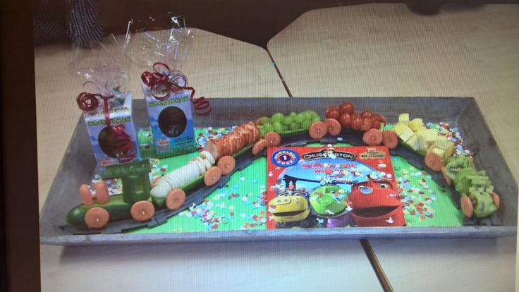 Gezonde traktatie trein van komkommer gevuld met hartige hapjes: schijfjes komkommer, kaas, druiven, worst, wortel etc.