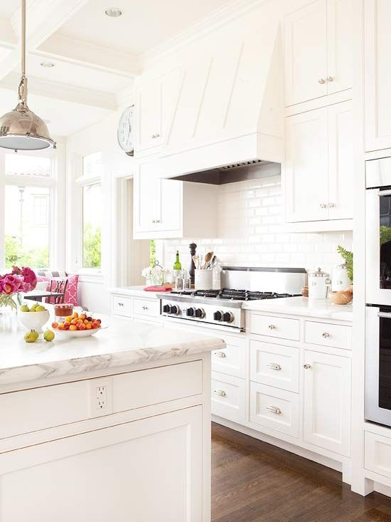 All white kitchen with subway tile backsplash, marble counters, chrome pendants over island, hardwood floors.