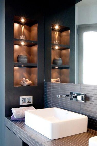 Avec des lumières d'ambiance qui soulignent leur présence, les petites niches de cette salle de bain ne manquent pas d'allure ! Voici des espaces de rangements ultra futés pour maximiser l'espace afin de pouvoir stocker vos affaires à proximité du lavabo. Une solution de rangement déco et tendance dans une petite salle bain design en nuance de gris.