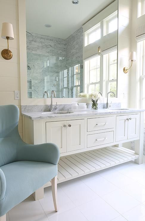 Vendome Single Sconces in Antique Brass illuminate an ivory framed mirror placed over an ivory dual washstand fitted with a slatted shelf topped with carrera marble fitted with his and her sinks and gooseneck faucets.
