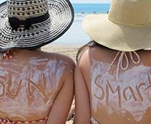 Two females with the words sun and smart in sunscreen on their backs