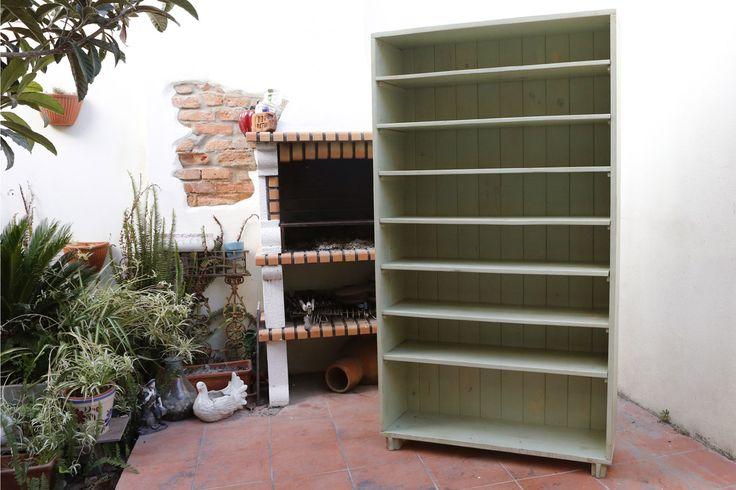Armário para arrumação de sapatos, feito com madeiras reutilizadas e com pintura desgastada.