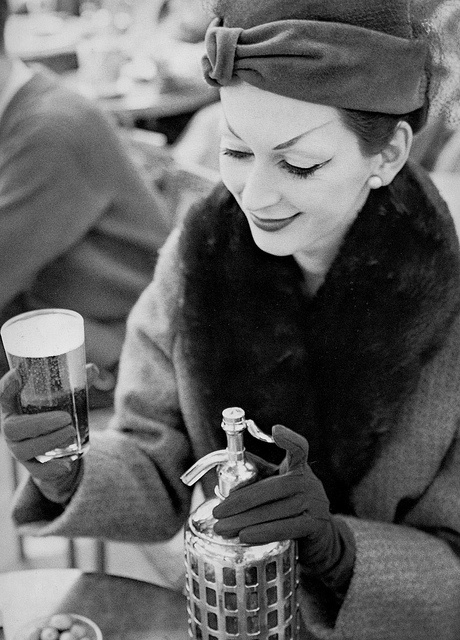 August 1955    Wearing a hat by Christian Dior. Photographed by Richard Avedon at Fouquet's, Paris.