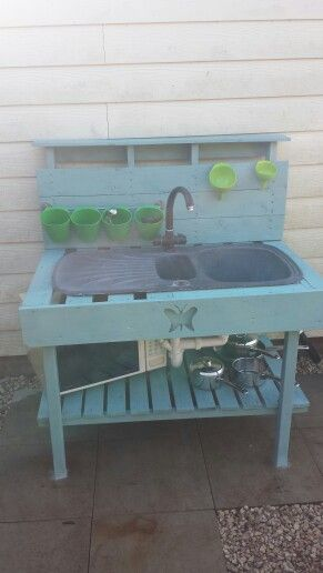 Mud kitchen made by my clever papa using old wooden pallets, up cycled sink, microwave and pots n pans. He's even plumbed it to connect with the hose to have running water and waste water is connected to the drain.  Rail and pots are from ikea.