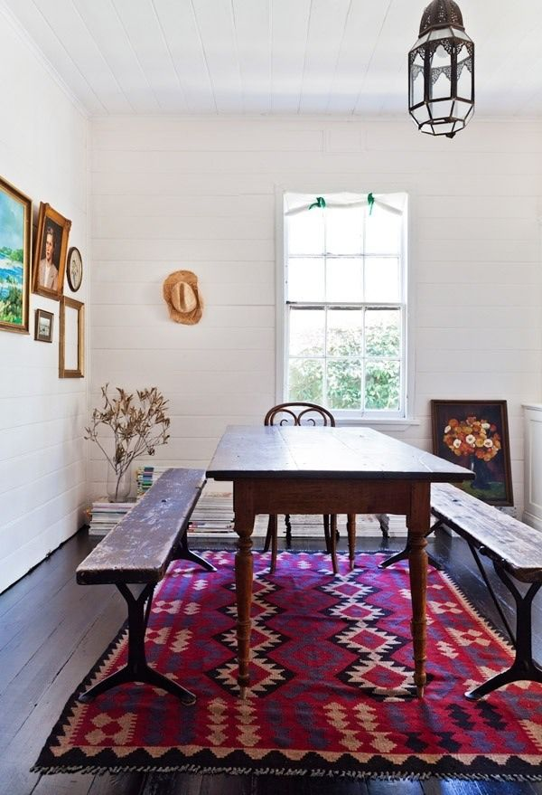 White Walls Antique Wood Dining Table With Long Benches And Bright Patterned Rug