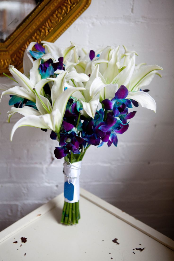 Wedding Bouquet with dog tag. White stargazer lilies and blue and purple orchids.