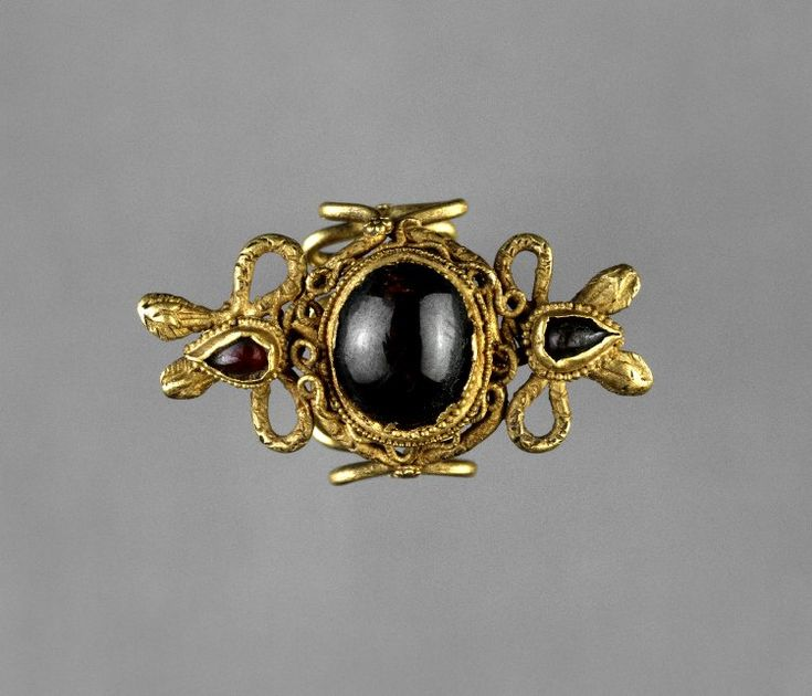 Egypt, 3rdC BC. Gold finger-ring with a large garnet in a setting of writhing snakes.