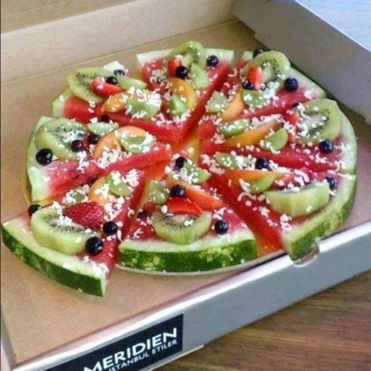 Foto: Gesunde Pizza  Wassermelone als Boden, verschiedene Früchte als Belag und Kokosnussraspeln als Käse.
