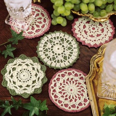 Subtly placed here and there, these five thread coasters will serve your guests with feminine charm. The table protectors are crocheted in complementary shades of rose and green and then topped with a layer of ecru lace for a coordinating finish. Our designs were crocheted with bedspread weight cotton thread (size 10) and a size 6 (1.80 mm) steel crochet hook. <p><strong>Number of Designs:</strong> 5 </p><p><strong>Approximate Design </p&g...