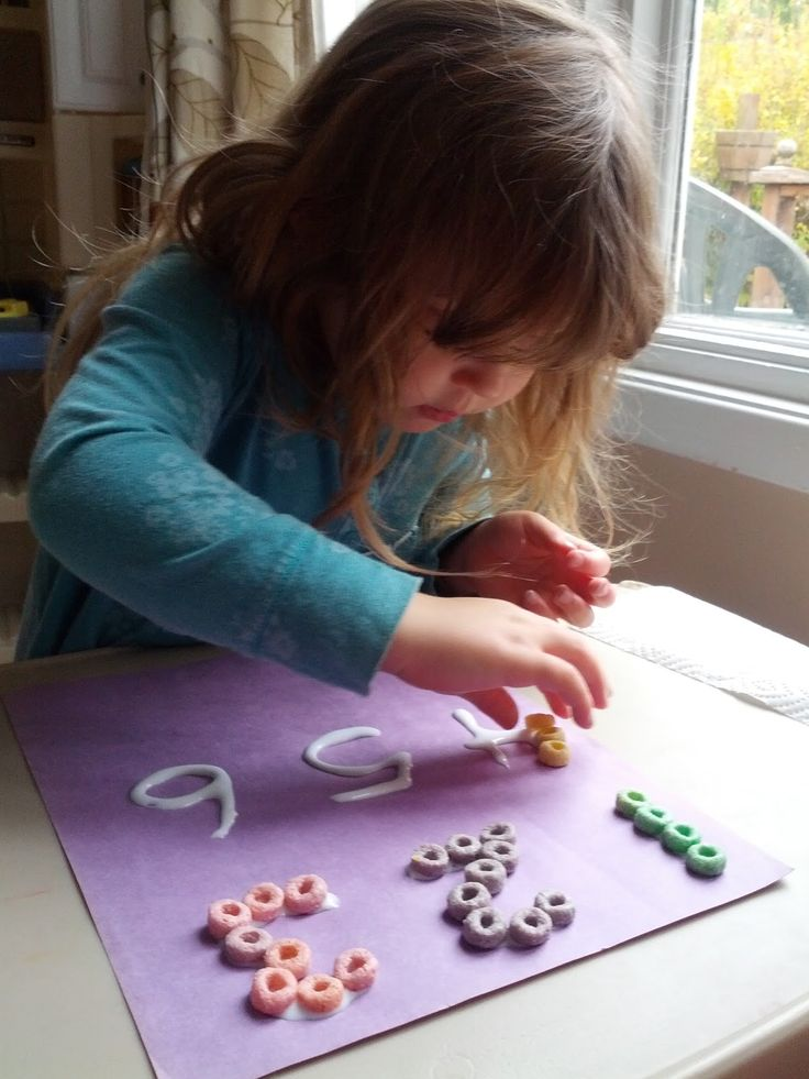 Practicing numbers couldn't be more fun than when you're playing with glue and Fruit Loops! When teaching little kids you always need to find fun new ways to keep their interest. Gluing things to paper is high on the list in our house! All we needed was construction paper white glue and colorful Fruit Loops. I wrote the numbers on the paper with the glue and Annika went to town placing the cereal on the glue.