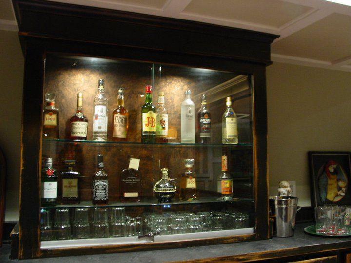 Custom built upper liquor cabinet in back bar area with sliding lockable glass doors > DMR Construction  317-674-5030