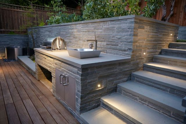What a fantastic way to utilize and easily decorate a contemporary outdoor kitchen space! The stone retaining walls add so much charisma to the scene. The cooking ware and sink add enough interesting perspective as it is, but the effortlessly cool surrounding area makes the outdoor kitchen that much more elegant. This would be an ideal setup for entertaining or hosting a cocktail barbecue. Perfect for those long summer nights.