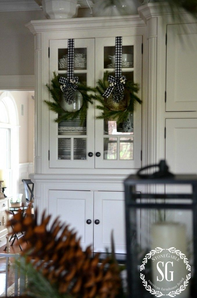 CHRISTMAS FARMHOUSE KITCHEN | Pine wreaths on black and white checked ribbons are also hung on some of my glass front cabinets. Simple and oh, so farmhouse!