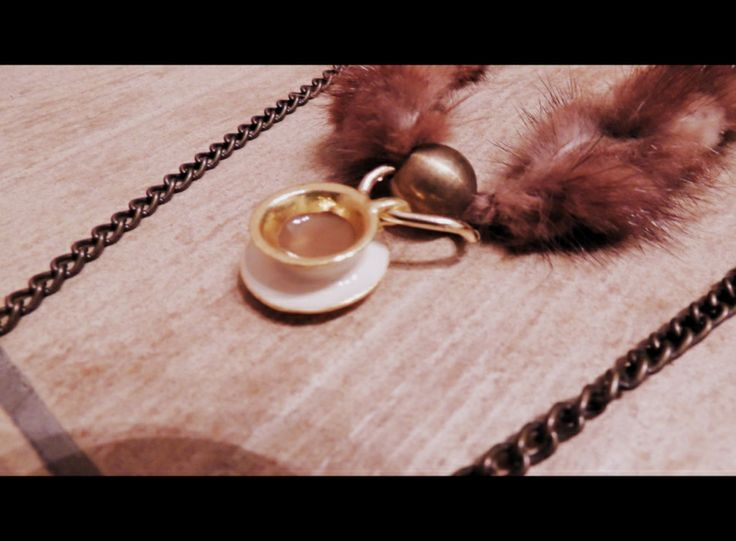 Handmade necklace with chains and a cup of coffee.