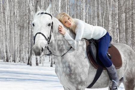 outdoor portrait of beautiful blonde girl sitting on pale horse in sunny winter forest