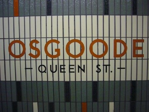 Sign reads OSGOODE in red TTC font and — QUEEN ST. — in black, set against cream-coloured vertical tiles