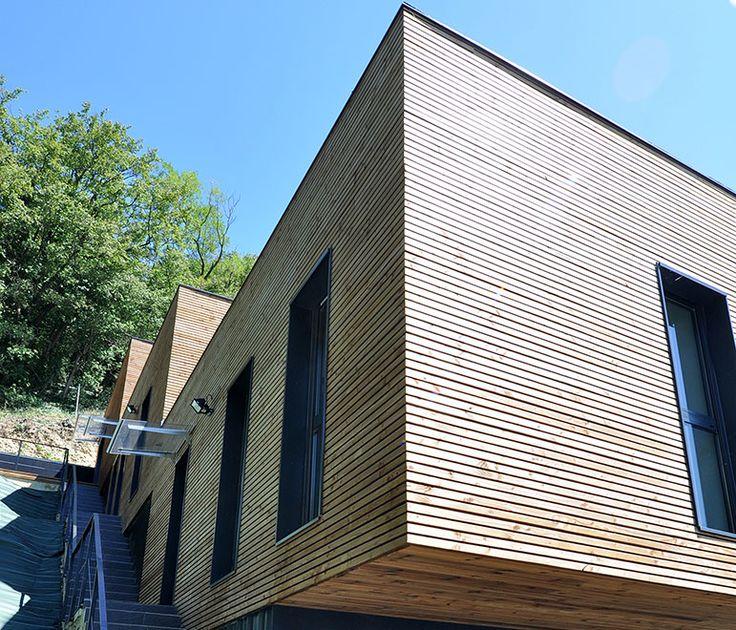 Composée de trois cubes de bois, cette maison vient se poser à côté duCorcovado Lyonnais : la Madone de Miribel, monument historique classé. Chaque cube de 50m², est revêtu de bardage en sapin Douglas chaufféqui contraste avec les menuiseries en aluminium laqué et le bardage métal des murs de soutènements en gris anthracite. Les cubes