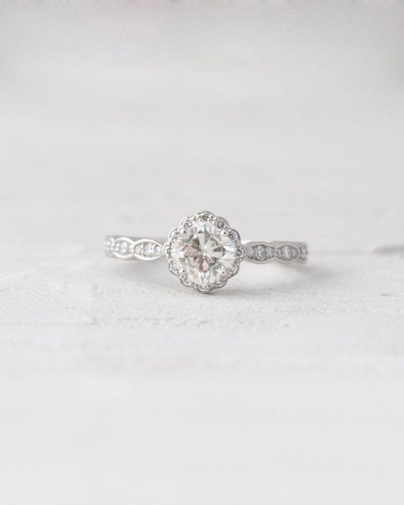 This a stunning vintage inspired ring with a delicate scallop detailing and accent diamonds radiating from the center stone, an antique