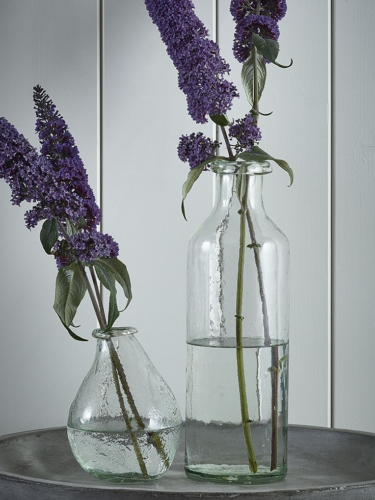 Crafted from recycled glass; this unique vase is a stylish take on a traditional alternative. Each weighty tall slim vase has been handmade, boasting individual charm and a rustic nature whether on its own or filled with flowers.