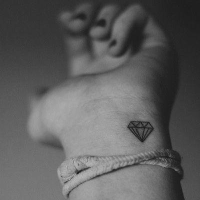 Pequeño tatuaje en la muñeca de un diamante.