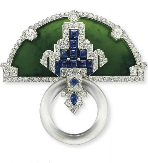 AN ART DECO JADEITE, DIAMOND, SAPPHIRE AND ROCK CRYSTAL BROOCH, BY CARTIER Designed as a half-moon shaped carved jadeite plaque, set with cabochon sapphires, trimmed with Old European, circular and single-cut diamonds, suspending an articulated carved rock crystal hoop, mounted in platinum, circa 1925 Signed Cartier