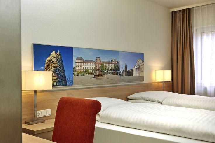 Liebevoll ausgewählte Details, wie die Bilder mit Darmstädter Motiv, sind in jedem Zimmer des H+ Hotel Darmstadt zu finden