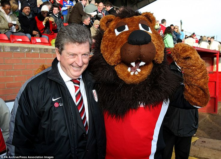 You have to wonder if then Fulham boss Roy Hodgson realises he is being photographed next to a six-foot-plus wild animal mascot here (Kettering Town mascot Champ the Lion) as he beams for the camera