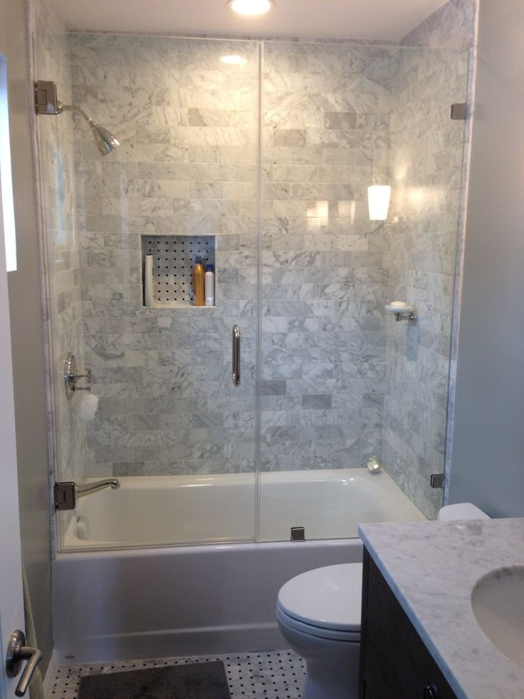 Frameless Tub Shower With Glass Doors Having Grey Ceramic Wall As Well As Small Bathtub And