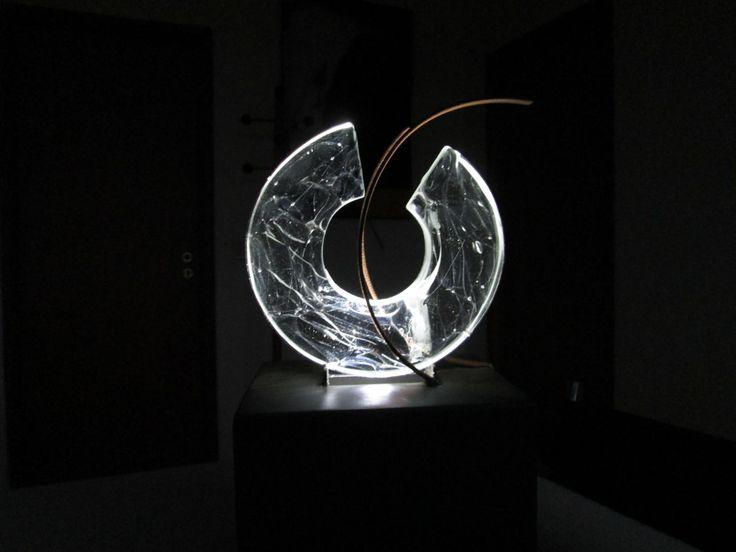 php6wohom.jpeg (Escultura),  20x40x4 cm por Conceição Cabral Uma peça em vidro fundido e maciço, diâmetro 20,  luminada  com ledes , base quadrada 20x20 em ferro pintado de preto.