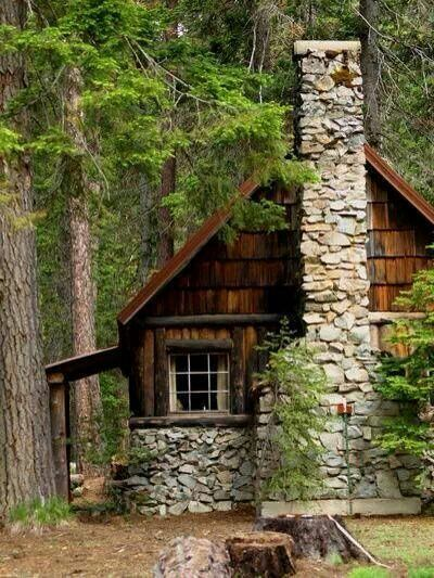 old rustic cabin in the woods with stone fireplace
