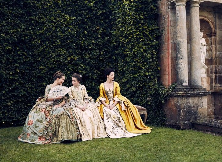 The second photo shows Claire sitting on a bench with Mary Hawkins (Rosie Day) and Louise de Rohan (Claire Sermonne) in all their finery.