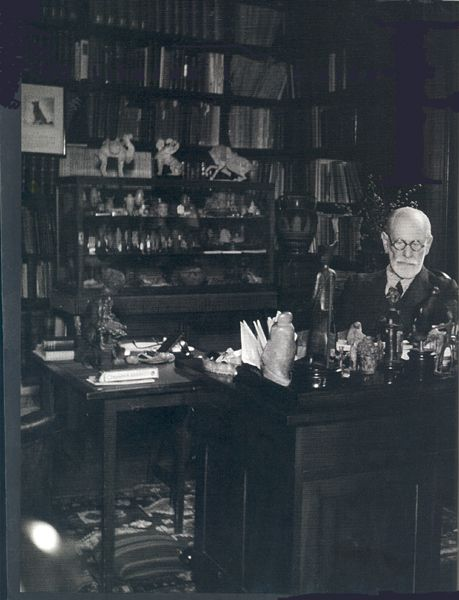 Sigmund Freud at his disk surrounded by his collection of antiquities, taken by Edmund Engelman 1938. Fascinated by archaeology, Sigmund Freud collected Egyptian, Near Eastern, Greek, Roman and Chinese artifacts, which he kept piled on shelves and tabletops. Freud's effects can now be seen at the Freud Museum, where his study and library are preserved as they were at the time of his death.    http://www.freud.org.uk/
