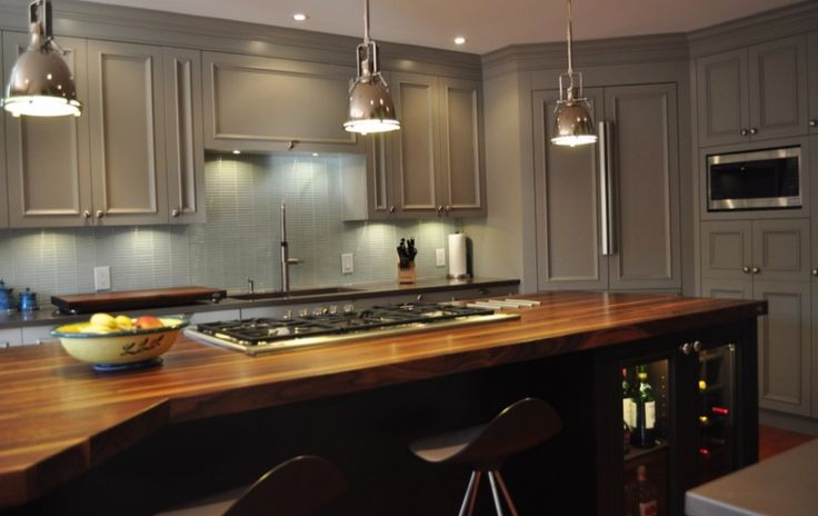 This exquisitely designed kitchen is a dream for the cooks and the guests.  With lots of countertop work space many stools for guests to sit and chat and a beautiful decor of chrome hanging lights over the island, neutral grey surrounding cabinets and backsplash tiles, natural wood countertop on the espresso island containing an illuminated liquor cabinet and mini wine cellar, this kitchen leaves nothing to desire.
