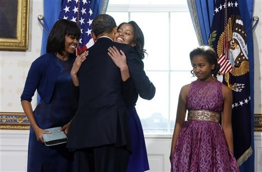 President Barack Obama hugs daughter Malia as first lady Michelle Obama and daughter Malia watch after Obama was officially sworn-in by Chief Justice John Roberts, not pictured, in the Blue Room of the White House during the 57th Presidential Inauguration in Washington, Sunday, Jan. 20, 2013. (AP Photo/ Larry Downing, Pool)    Read more here: http://www.kansascity.com/2013/01/12/4017322/the-presidential-inauguration.html#storylink=cpy